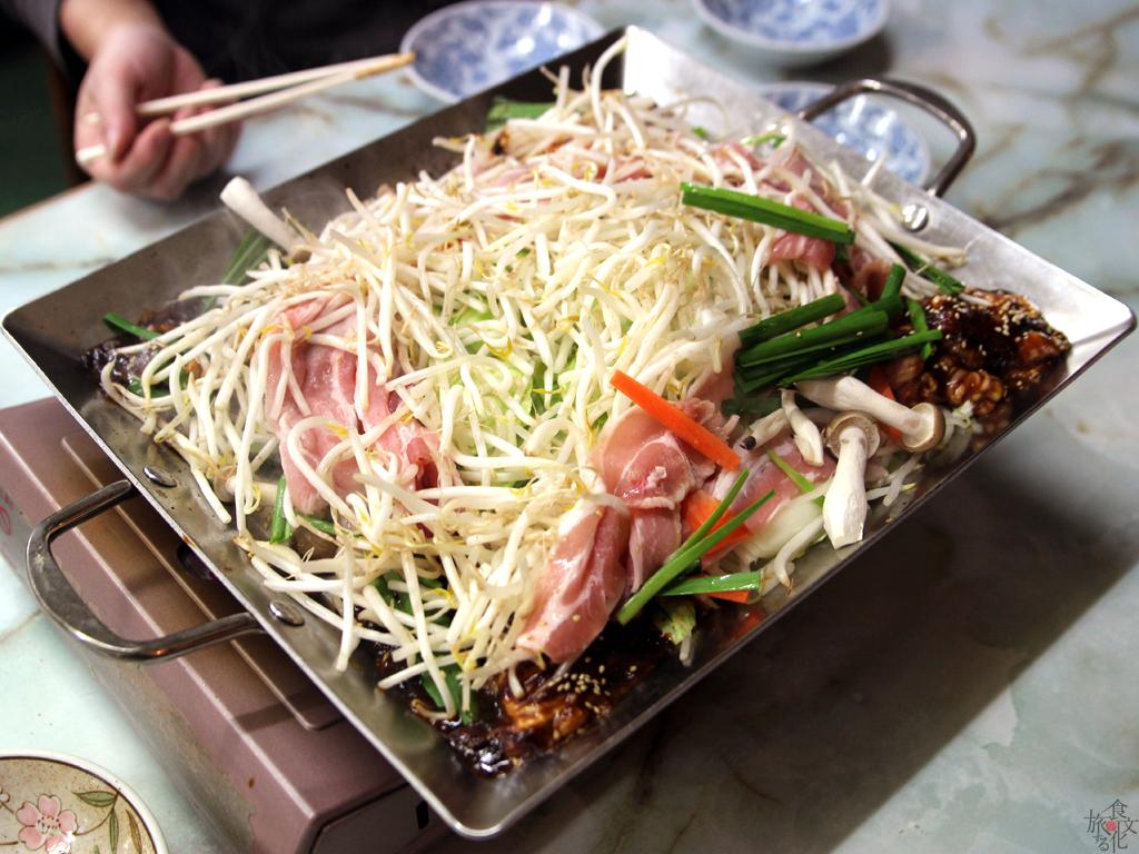 野菜と肉の山を崩し、全体を炒めていく